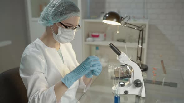 Thumbnail for Female Doctor In Laboratory With Microscope And Chemical Test Tubes