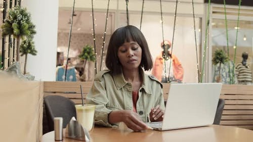Pretty African Woman Using Laptop in Cafe in Shop