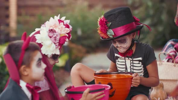 Kinder in Halloween-Kostümen sitzen draußen nach Trick-oder-Behandlung