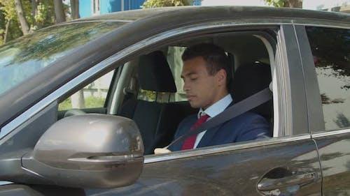 Black Businessman Fastening Seat Belt in Car
