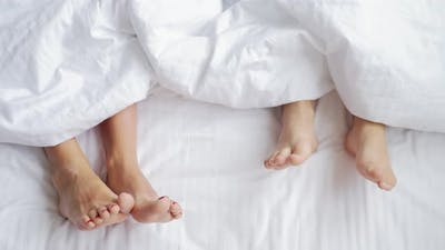 Mother and Child Lie on Bed with White Sheets Feet Side By Side in Comfortable Bed at Home