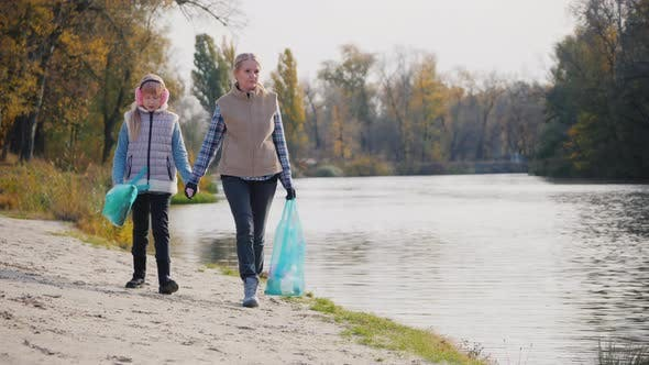 Thumbnail for Woman Volunteer with a Child Walk Along the Lake, Carry Packages with Garbage.