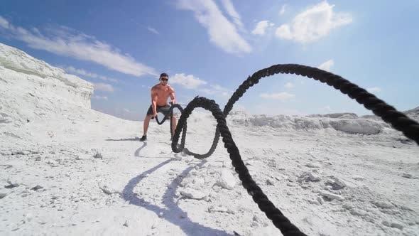 Bodybuilder exercising with battling ropes