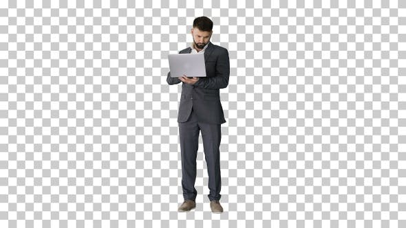 Thumbnail for Handsome businessman standing and working on laptop, Alpha Channel
