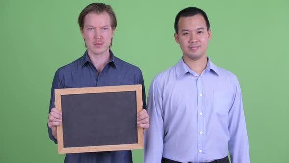 Thumbnail for Two Happy Multi Ethnic Businessmen Holding Blackboard and Giving Thumbs Up