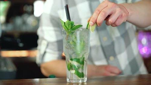 Barman schmückt einen fertigen Cocktail