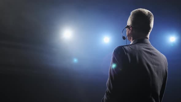 Thumbnail for Rear View of Men Speaking Through a Microphone in Dark Conference Hall. Man Talks Into Microphones