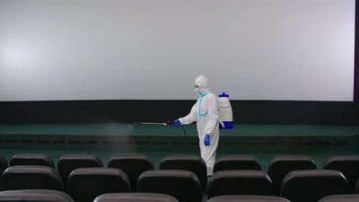 Worker Cleaning Cinema Hall with Against Coronavirus