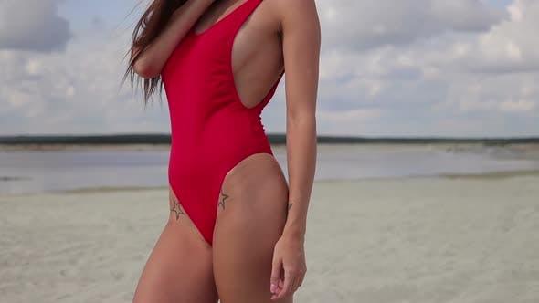 Cover Image for Sinnliche Frau in rot Bikini stehend und genießen Sonnenschein