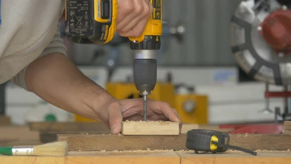 Thumbnail for Carpenter drilling holes in a piece of wood