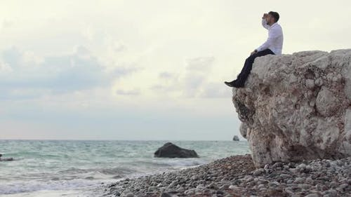 Handsome Stylish Man Sitting on the Rocks and Watching an Amazing View