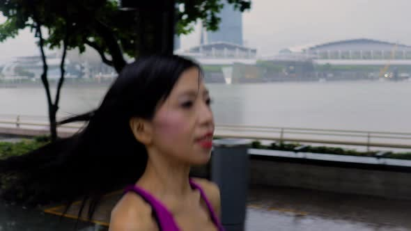 Middle-aged Asian woman jogging in the rain in Singapore