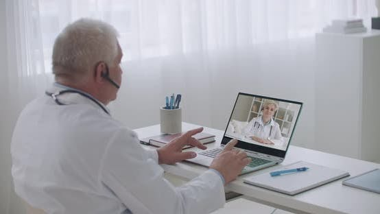 Thumbnail for Therapist and Infectious Diseases Specialist Are Consulting Each Other By Video Call From Offices in
