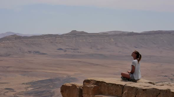 Thumbnail for Young Woman in Sunglasses Sitting on Cliff's Edge and Looking Around the Desert