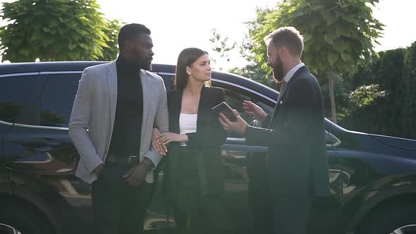 Thumbnail for Salesman Presenting a New Car to Young Couple in Outdoors
