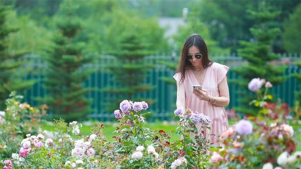 Thumbnail for Young Girl in a Flower Garden Among Beautiful Roses, Smell of Roses