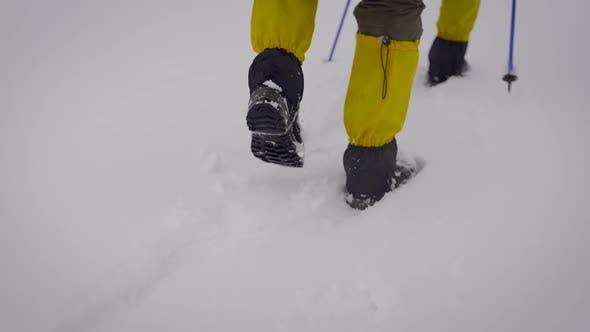 Thumbnail for Zwei Männer gingen auf eine Expedition. Professionelle Trekkingstiefel und Leggings Hilfe, sich im Schnee zu bewegen.