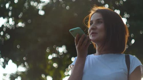 Mädchen mit Smartphone-Spracherkennung diktiert Gedanken Sprachwahl bei Nacht Abend