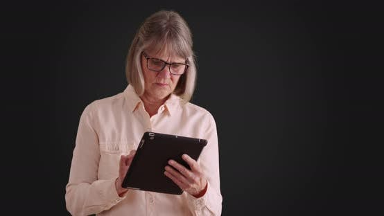 Independent senior woman using tablet device to browse online on gray backdrop