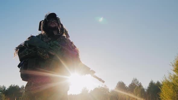 Thumbnail for The Soldier in the American Ammunition Worth Against the Sky. The Sun Shines on His Arms