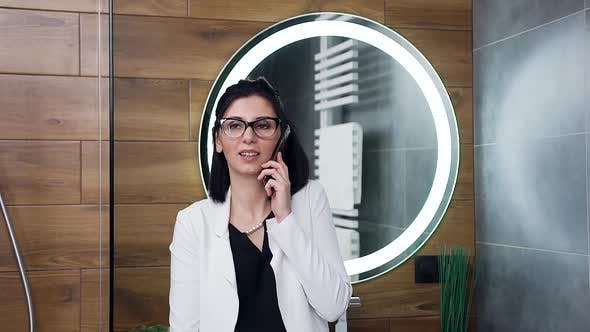 Business Lady in White Suit which Has Mobile Conversation in Her Home Bathroom