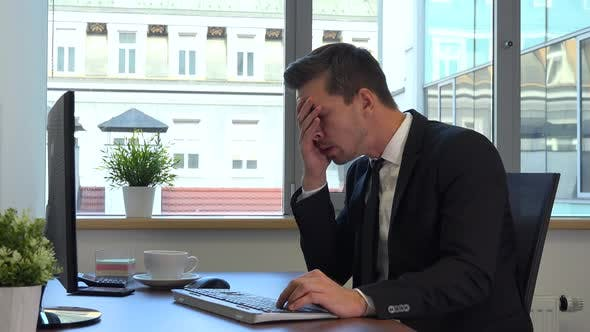 Thumbnail for An office worker in a suit in front of a computer gets upset