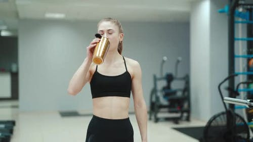 A slender woman in a black sports top and with her hair stuck in the tail is drinking water