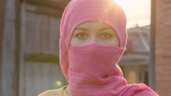 Attraktive muslimische Frau mit natürlichem Make-up, das rosa Hijab-Schal trägt, schaut in die Kamera