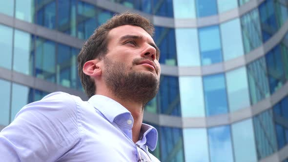 Thumbnail for A Businessman Stands in Front of an Office Building and Looks Around Proudly - Closeup From Below