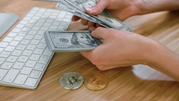 Female Hands Counting Cash with Bitcoins