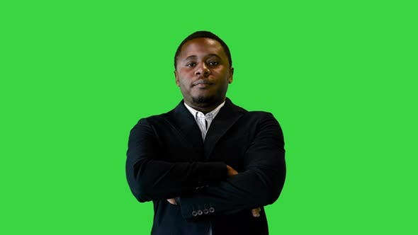 Handsome Black Man in Black Jacket Smiling and Pointing a Finger on a Green Screen Chroma Key