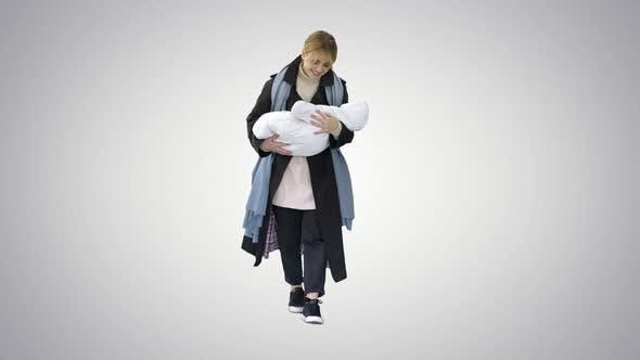 Mutter geht mit Baby in ihren Händen auf Farbverlaufshintergrund.