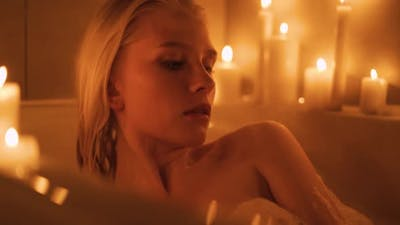 Woman Relaxing in Luxury Spa Bath Decorated with Candles