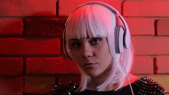 Thumbnail for Sexy Unusual Girl in White Wig Listening To Music Using Headphones, Red Light Brick Wall