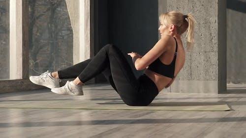 Frau stärkt die Muskeln der Presse mit einer Last von Übungen