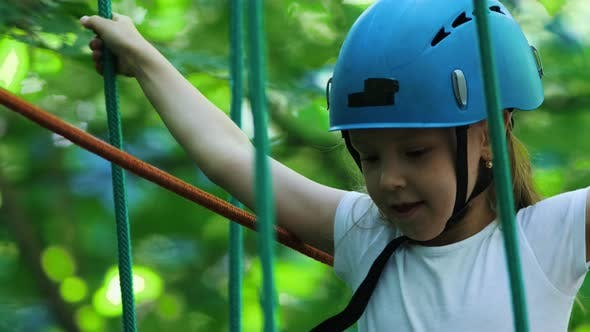 Thumbnail for Rope Adventure in the Park - a Little Girl in Helmet Moving Over the Rope Bridge on High