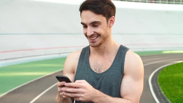 Thumbnail for Closeup Runner Standing with Smartphone on Track. Sporty Man Holding Phone