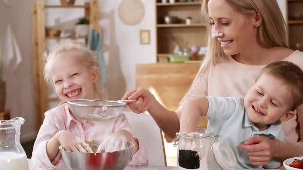 Happy Caucasian Housewife Making Batter with Kids