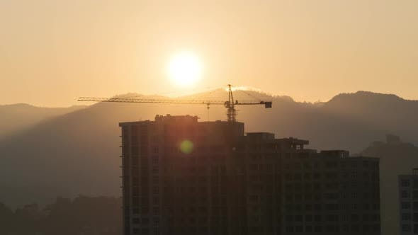 Sunrise Over a Tower Crane on Construction Site with a Skyscraper in the City, Timelapse