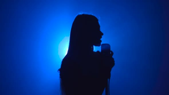Girl Sings Songs for the Clip. Smoke Background. Silhouette. Side View