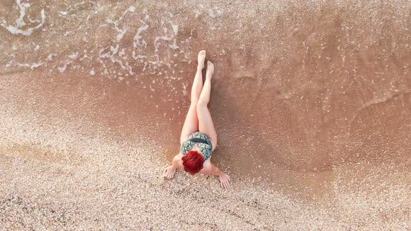 Thumbnail for Top View Young Woman in a Swimsuit Sitting on a Sandy Beach Her Legs Caressing the Surf