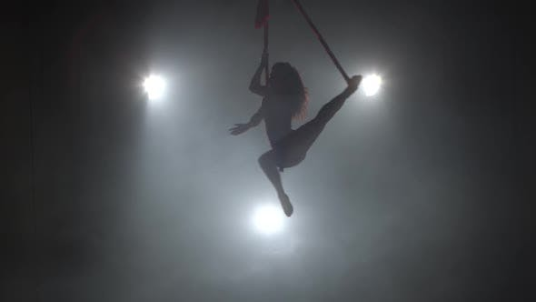 Silhouette Beautiful Woman Dancing with Aerial Silk on a Three Rays Background 051