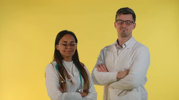 Multiracial Male and Female Doctors Nodding Their Heads To the Camera on Yellow Background.