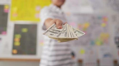 Hand man giving cash money to businessman