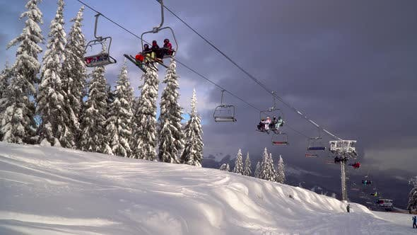 Thumbnail for Ski Lift Carries Skiers and Snowboarders on the Mountain