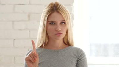 Young Woman Waving Finger to Refuse
