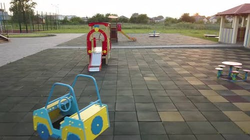 Footage on preeschool yard with swings, slides and modern daycare school building.