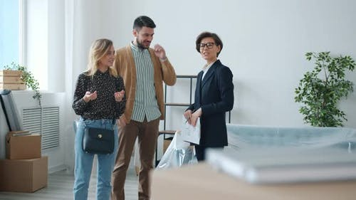 Professional Realtor Talking To Customers Man and Woman Showing New Apartment