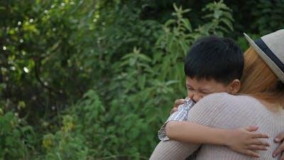 Happy family mom hugging her son