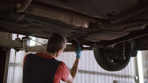 Auto Mechanic Repairs Car on the Lift in the Service Station